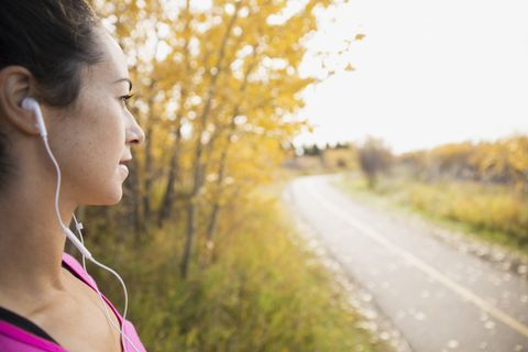 Jogger with headphones looking at autumn path