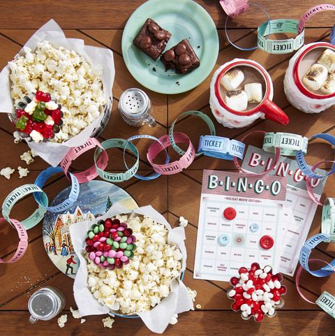 a tabletop filled with popcorn and candy and a movie ticket garland