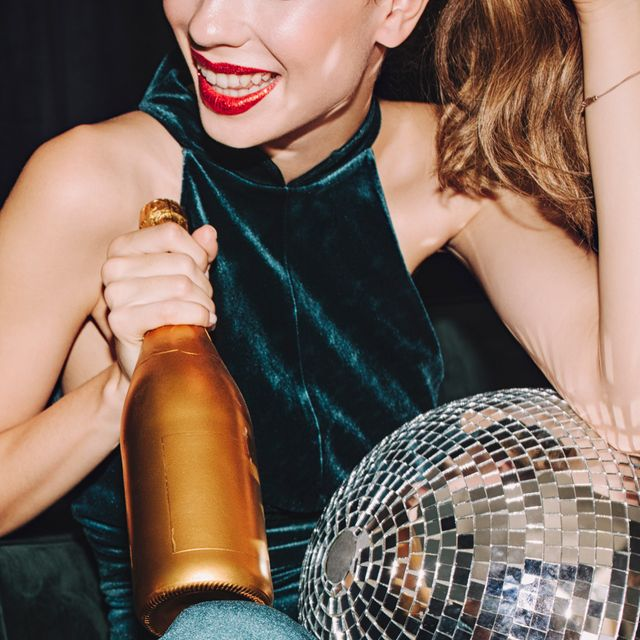 woman in dark green velvet dress with disco ball and champagne