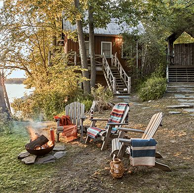 a trio of adirondack chairs set up around a fire pit