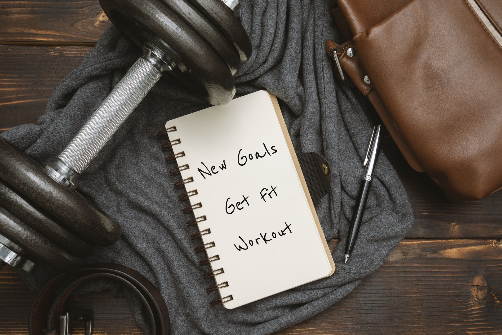 New Year's Goals and Resolution Written on Notepad, with Dumbbell and Satchel Man's Bag on Rustic Wood