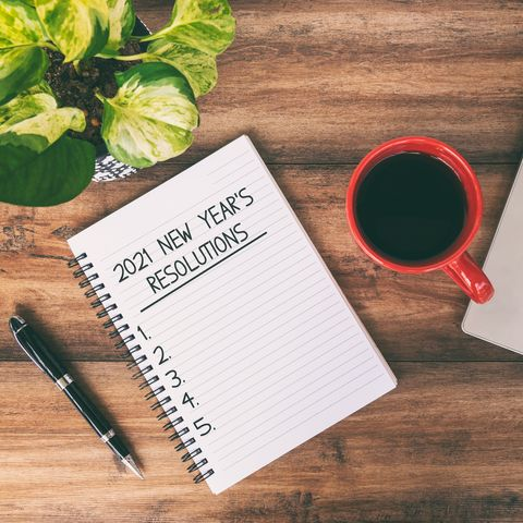 2021 new year's resolutions text written on notepad with laptop and cup of coffee on top of wooden desk