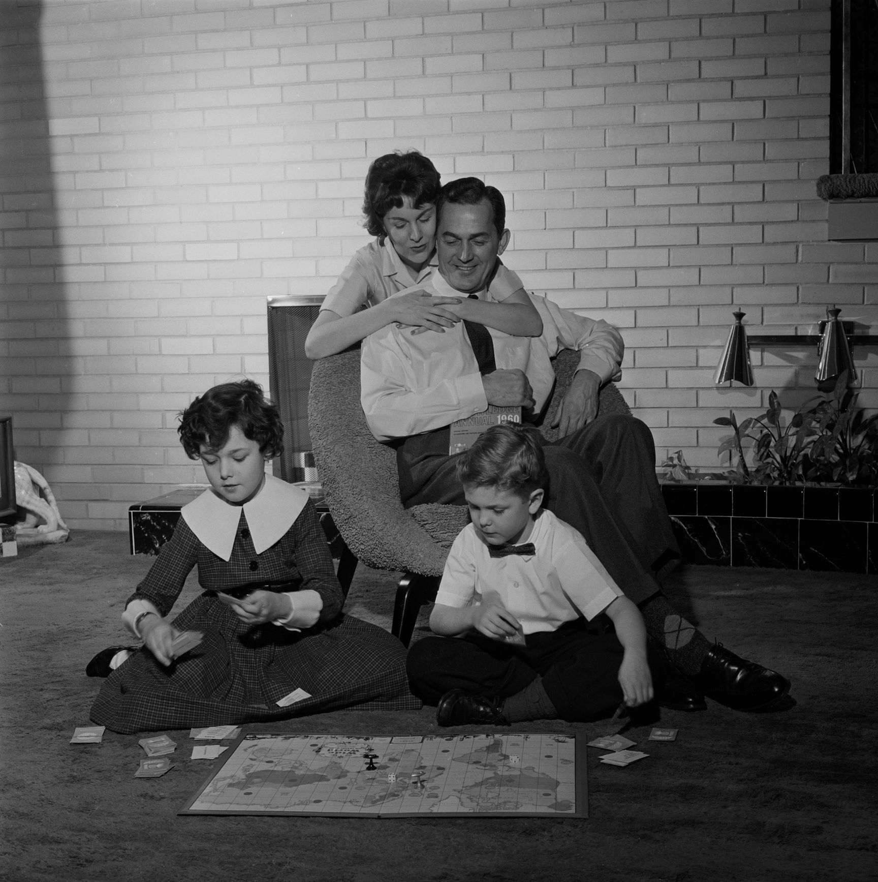 USA, New York, New York City, Parents looking at kids (4-5) playing board game