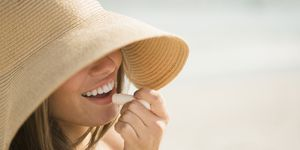 USA, New York State, Rockaway Beach, Woman wearing sun hat applying lipstick
