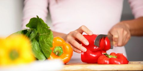 Only 23% of Americans serve vegetables at dinner; woman chopping vegetables