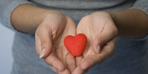 helping others can relieve stress; woman holding a heart cut-out