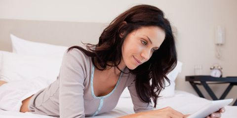 woman on bed with tablet computer