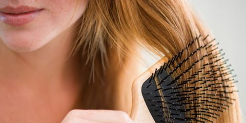 Hair loss might be helped by a glaucoma medication; woman brushing hair