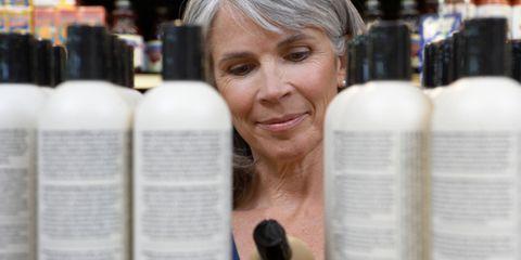 Woman reading shampoo ingredient label