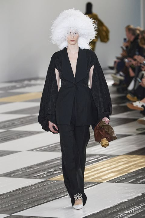 A model wears a black suit, featuring a blazer with open, puff sleeves. The outfit is style with off-white ballet flats, a white puff hat, and a multi-colored brown clutch bag.