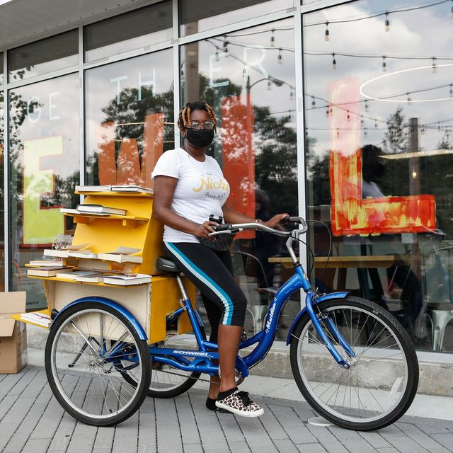 cetonia weston roy sits on her bookstore tricycle with books on display