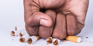 Cropped Hand Of Man Crushing Cigarette On White BackgroundBenefits of quitting smoking