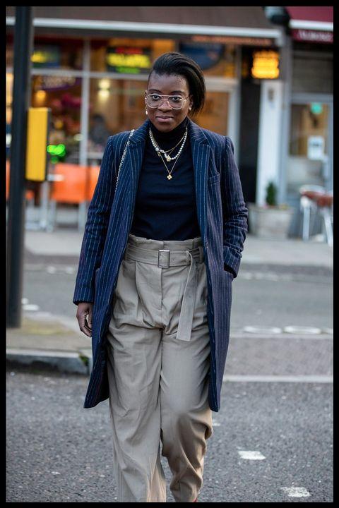 nikki ogunnaike wears plaid trousers and a longline coat to new york fashion week