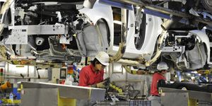 Nissan Motor's workers install a battery