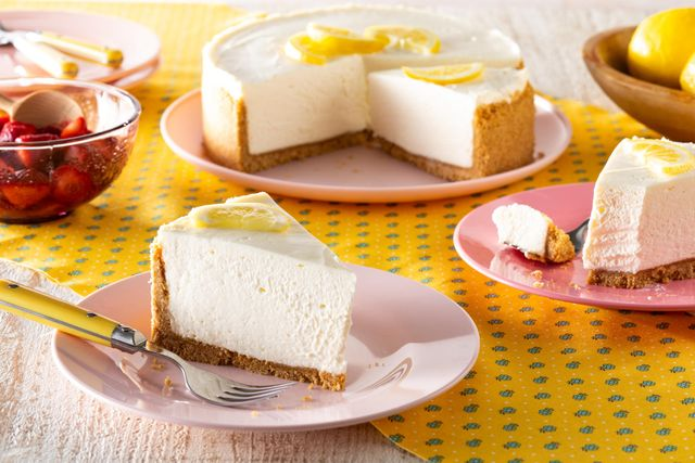 no bake lemon cheesecake slice in front with whole cheesecake lemons and strawberries in back