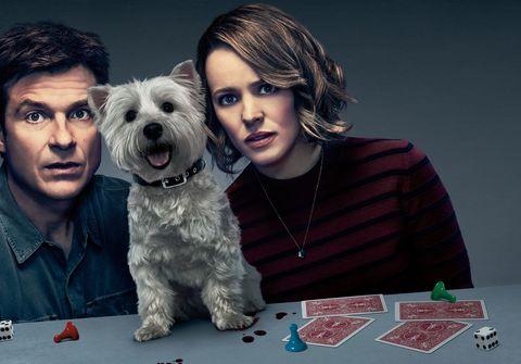 una pareja con su perro y unas cartas en la película noche de juegos