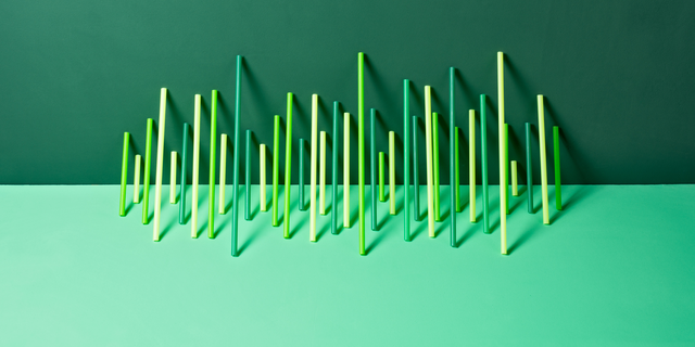 uneven green plastic pipes leaning on green colored background front view