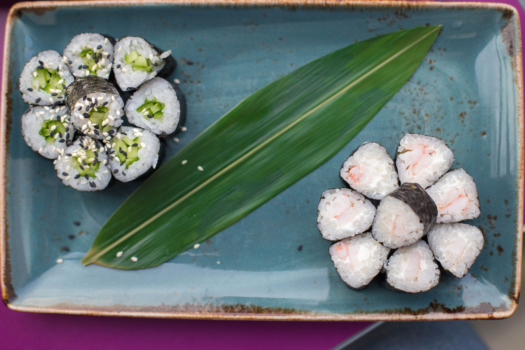 Vegetarian sushi with rice and vegetables on turquoise ceramic dishes.