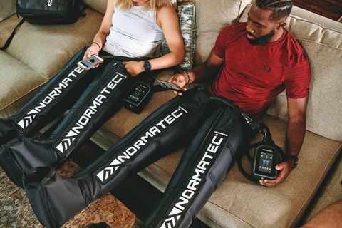 two people sit on couch in normatec boots