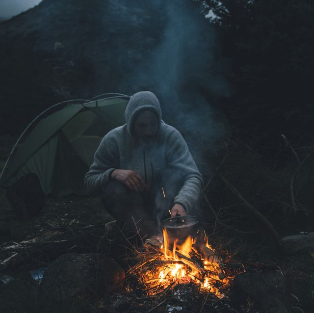 Norway, Lofoten, Moskenesoy, Young man sitting at camp fire