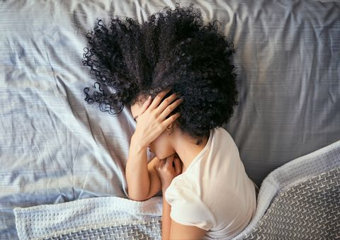 vrouw met migraineaanval ligt in bed