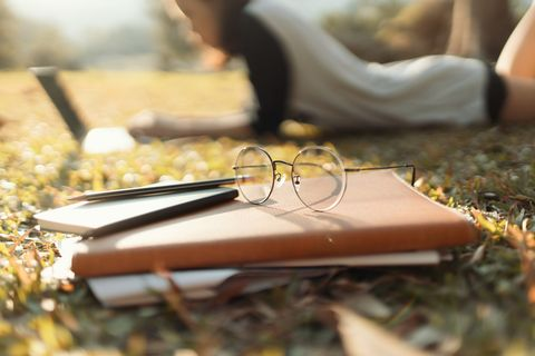 notebook and eye glasses of student with female student working background