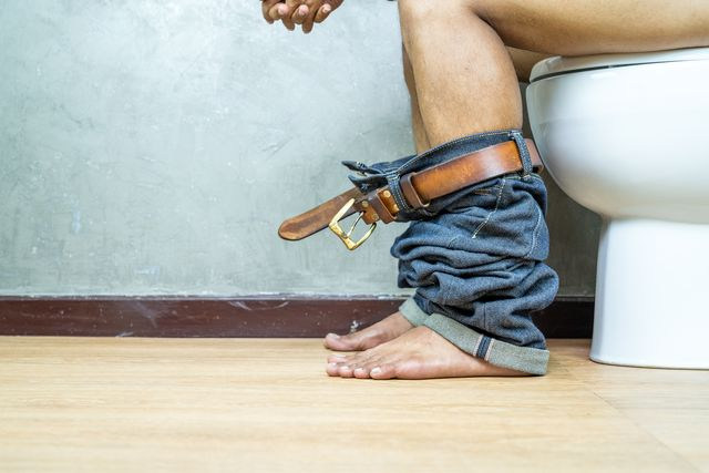 nude picture, man sitting on toilet bowl in the toilet, constipation concept