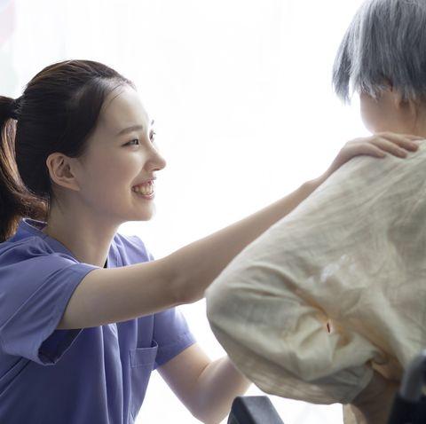 nurse assisting senior woman in wheelchair