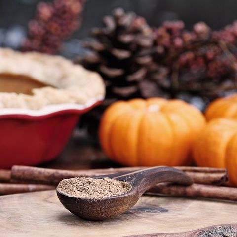 pumpkin pie spice measured in a wooden spoon over a rustic wooden background pie and pumpkins in the background