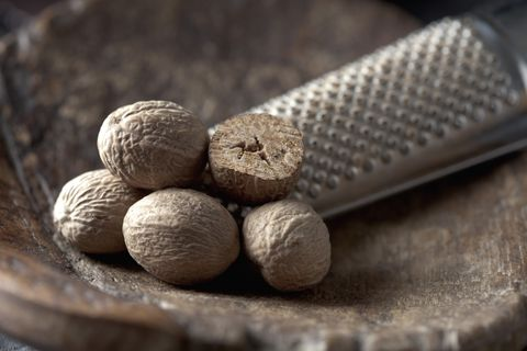 nutmegs with grater on wooden spoon, close up