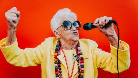 Levendige bejaarde vrouw zingt in microfoon