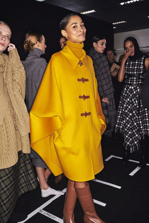 Fashion model, Clothing, Yellow, Fashion, Outerwear, Fashion design, Event, Coat, Overcoat, Footwear,