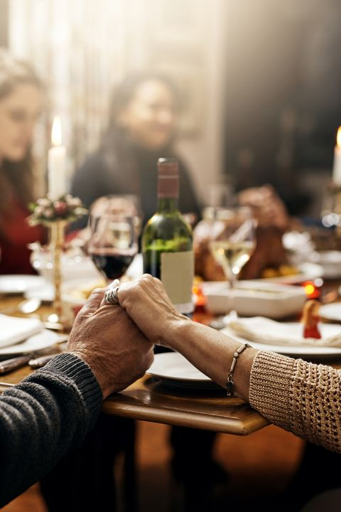 shot of family holding hands in prayer before having a christmas lunch together