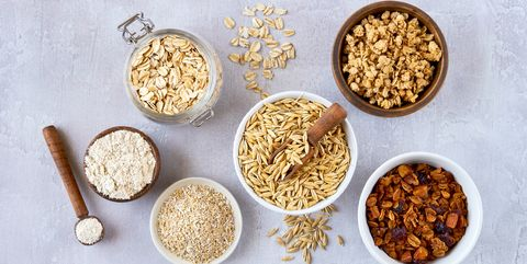 oat products assortment in bowls  granola, rolled oats, bran , flour and raw oat seeds  top view