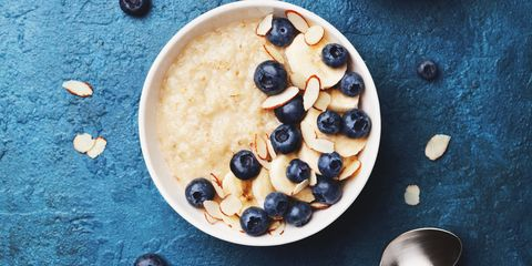 Oatmeal porridge with banana and blueberry on vintage table top view in flat lay style. Hot breakfast and diet food.