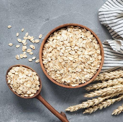 oats, rolled oats or oat flakes in wooden bowl