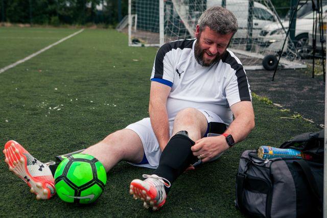 un hombre obeso se prepara para jugar un partido de fútbol