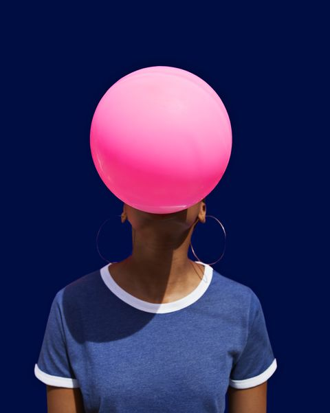 obscured face of woman blowing balloon