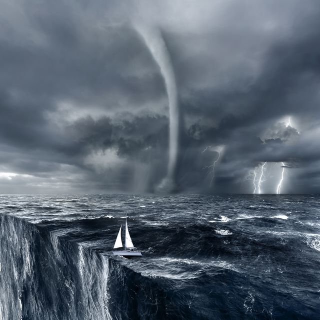 ocean with sailing boat with waterspout and hurricane