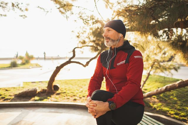 wellbeing and vitality, active healthy lifestyle of elderly people mature man with beard training outdoors in park in morning stretching and warming up body serious and concentrated winter season