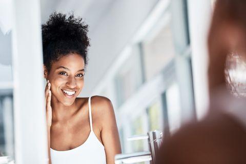 vrouw lachend naar zichzelf in de spiegel