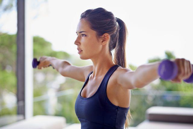 vrouw traint schouders en nek met dumbells