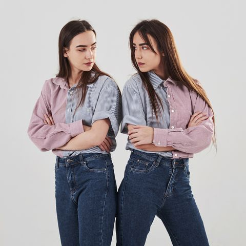 offended and look at other with anger two sisters twins standing and posing in the studio with white background
