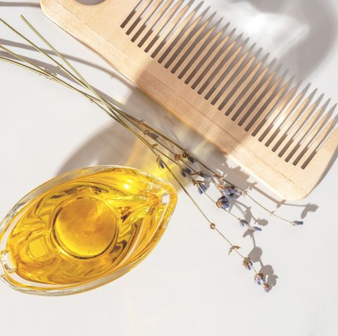 oil, wooden comb and dry lavender on a light background