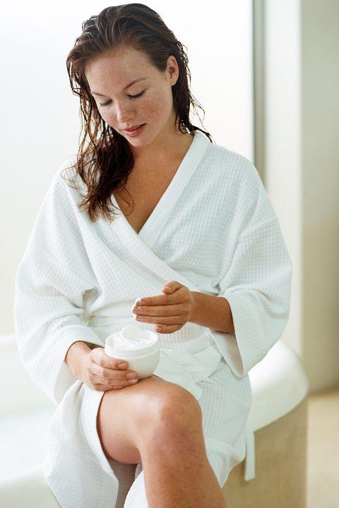 Young woman applying moisturiser