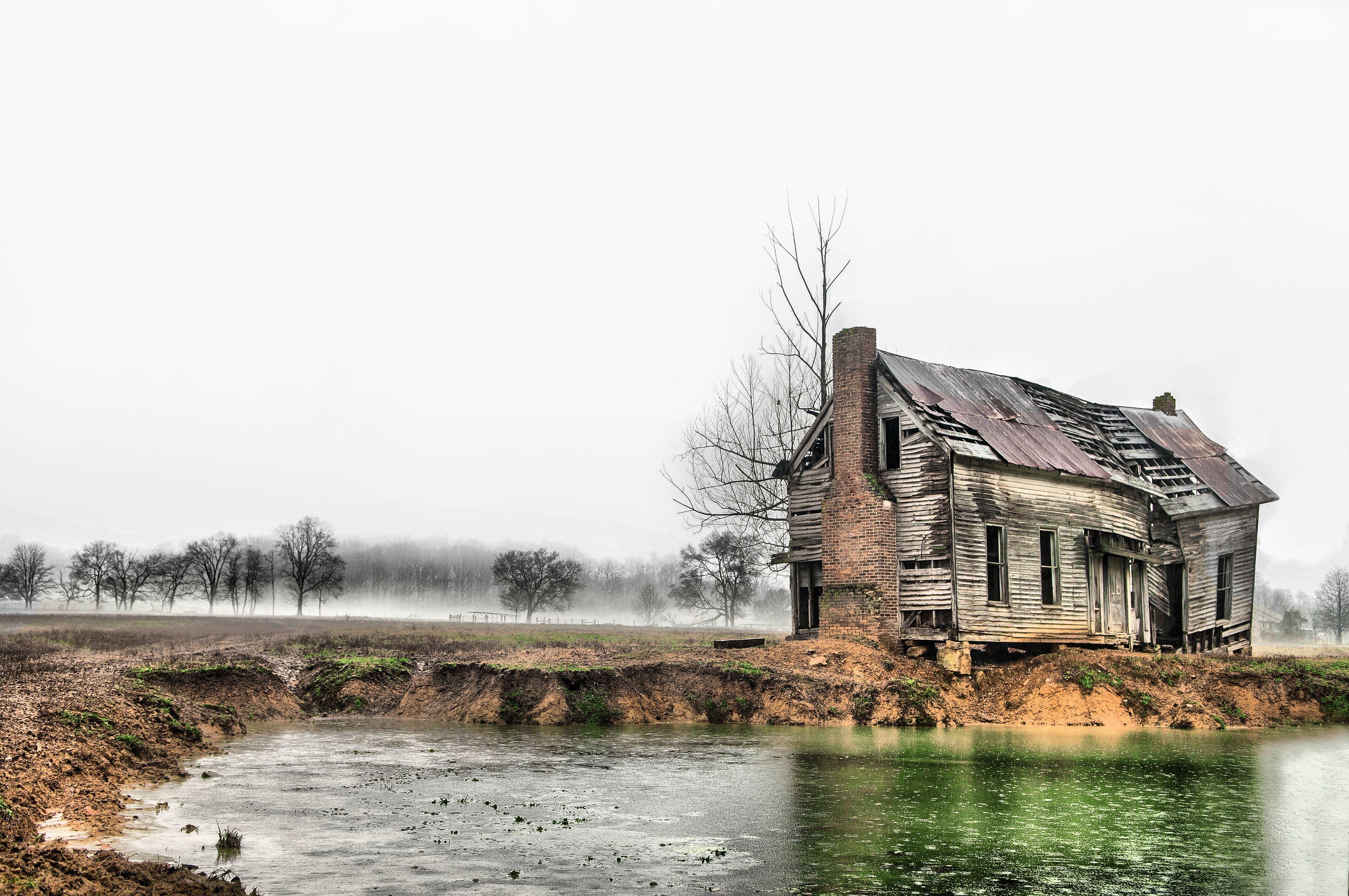 gammelt hus ved dam mot himmelen