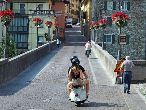 old vintage vespa and pedestrians cross the ancient devil bridge, in the center of cividale del friuli, italian town