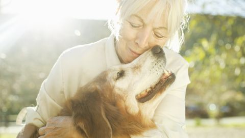 old woman hugging dog
