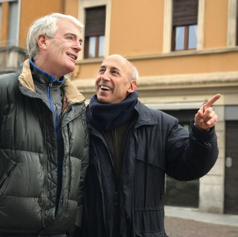 winter date ideas - Older Gay Male Couple Walking Along Quaint Historic Street, Talking, and Pointing