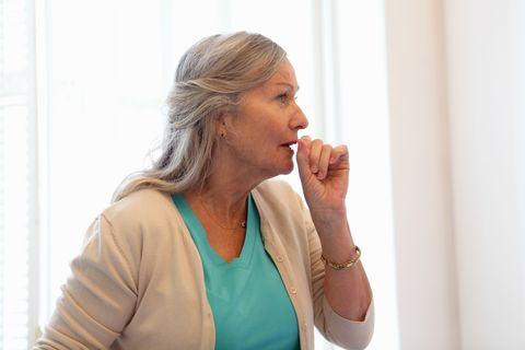 Older woman coughing into her hand